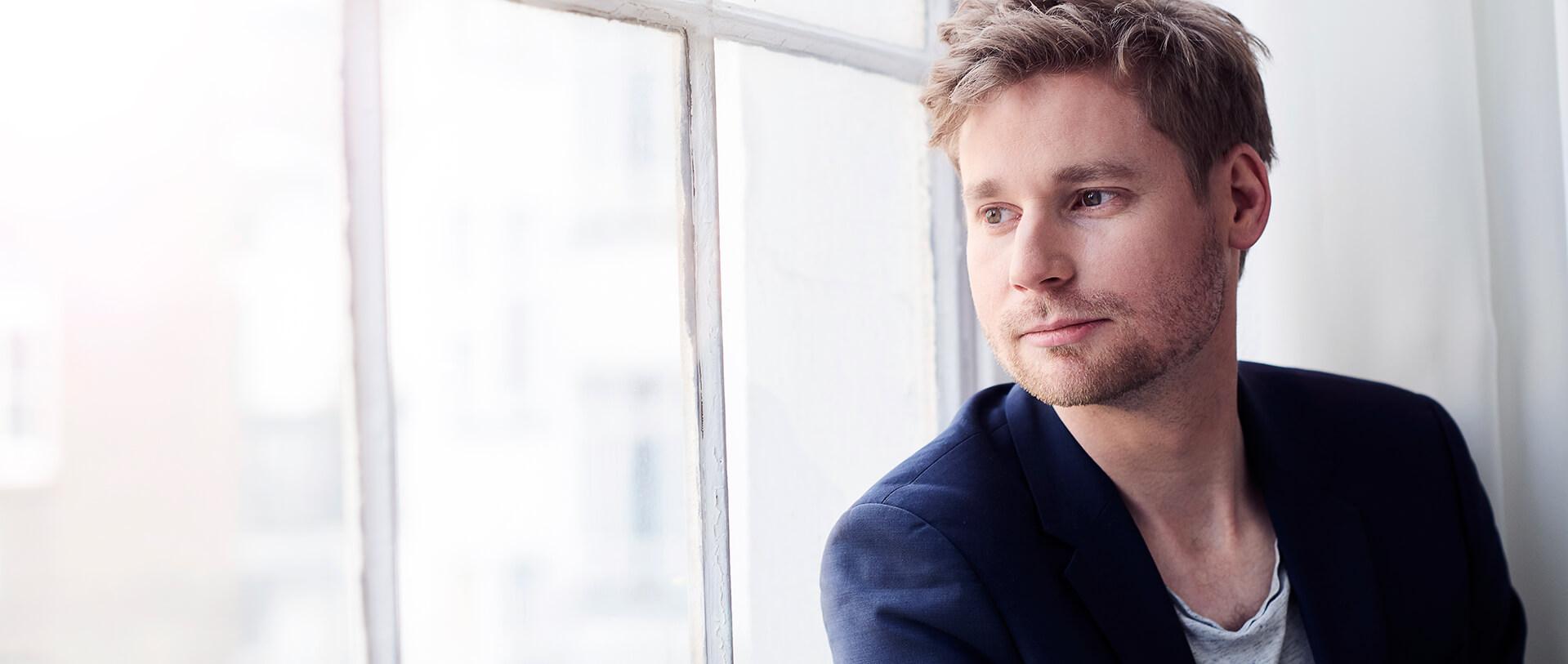 Erik Flügge schaut aus einem Fenster